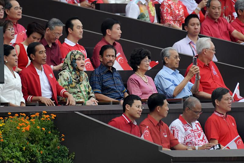 Indonesia's President Joko Widodo (centre 2nd L) and his wife Iriana (centre L), Brunei's Sultan Hassanal Bolkiah (C), Malaysia's Prime Minister Mahathir Mohamad (centre 2nd R) and his wife Siti Hasmah Mohamad Ali (centre 3rd R) attend the 54th National Day Parade in Singapore on August 9, 2019. (Photo by Roslan RAHMAN / AFP) (Photo credit should read ROSLAN RAHMAN/AFP/Getty Images)
