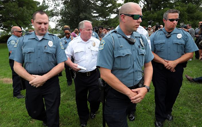 Ferguson Police Chief Tom Jackson is surrounded by his officers as he leaves a news conference in August. (AP/St. Louis Post-Dispatch, Robert Cohen)