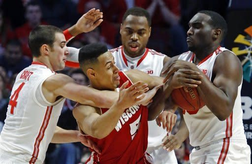 Ohio State forward Evan Ravenel, right, takes the ball away from Wisconsin forward Ryan Evans (5) during the first half of an NCAA college basketball game in the championship of the Big Ten tournament Sunday, March 17, 2013, in Chicago. At left is Ohio State guard Aaron Craft (4), and behind Evans is Ohio State forward Deshaun Thomas. (AP Photo/Charles Rex Arbogast)