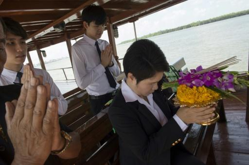 Medical students pray on the boat during the ceremony
