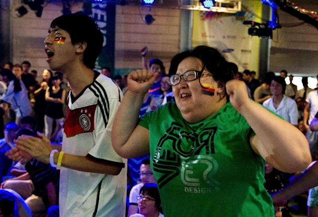 Chinese soccer fans celebrate after Germany scored a goal against Argentina as they watch the World Cup final match between Germany and Argentina at the 2nd Live Arena in Beijing, China Monday, July 14, 2014. (AP Photo/Andy Wong)