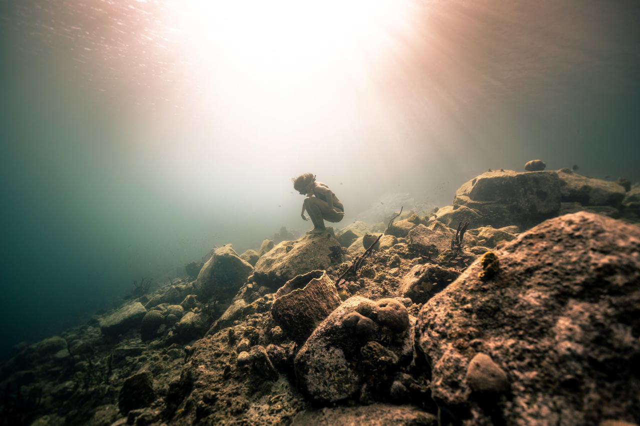 <p>A diver sits on rocks on the ocean floor as the sunlight beams through the water. (Photo: Alex Voyer/Caters News) </p>