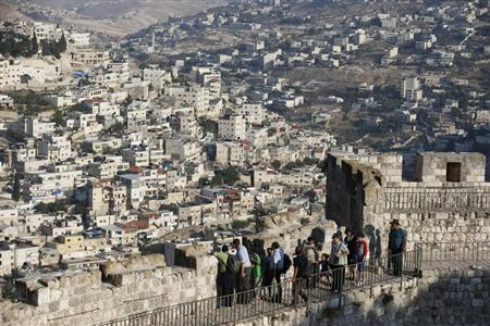 Arab neighbourhoods in East Jerusalem are seen in the background as tourists walk atop a wall surrounding Jerusalem's Old City