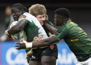 South Africa's Sakoyisa Makata, right, gets his hand to the face of teammate Christie Grobbelaar, back, as they tackle Kenya's Alvin Otieno during an HSBC Canada Sevens rugby game in Vancouver, British Columbia, Saturday, Sept. 18, 2021. (Darryl Dyck/The Canadian Press via AP)