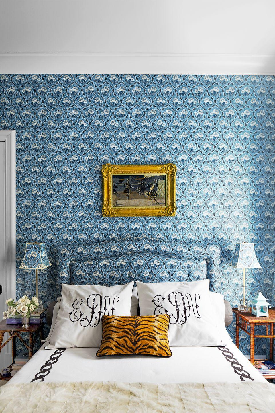 "<p><a href=""https://www.housebeautiful.com/design-inspiration/home-makeovers/tips/a2226/ellen-niven-interview-0514/"" rel=""nofollow noopener"" target=""_blank"" data-ylk=""slk:Ellen Niven"" class=""link rapid-noclick-resp"">Ellen Niven</a> took inspiration from traditional Provençal hotels, padding the walls, swathing the headboard and lampshades at her Long Island home in Le Manach's Balmoral blue floral pattern, and hanging a gilt frame. The monogrammed pillows mark a personal touch while the tiger-print throw spices the room up. </p>"