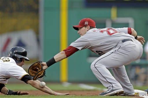 Pittsburgh Pirates' Neil Walker, left, dives back safely to first as the pick-off throw from Houston Astros pitcher Bud Norris gets past first baseman Chris Johnson (23) during the first inning of a baseball game in Pittsburgh on Thursday, July 5, 2012. (AP Photo/Gene J. Puskar)