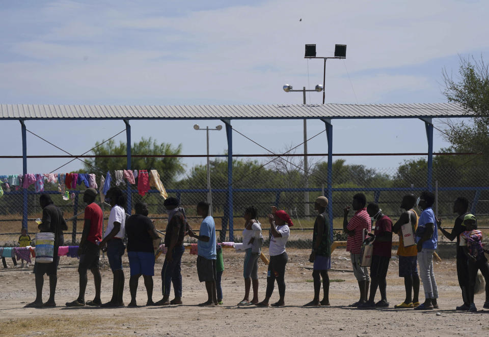 Migrants, many from Haiti, line up to receive food at an improvised refugee camp at a sport park in Ciudad Acuña, Mexico, Wednesday, Sept. 22, 2021, (AP Photo/Fernando Llano)