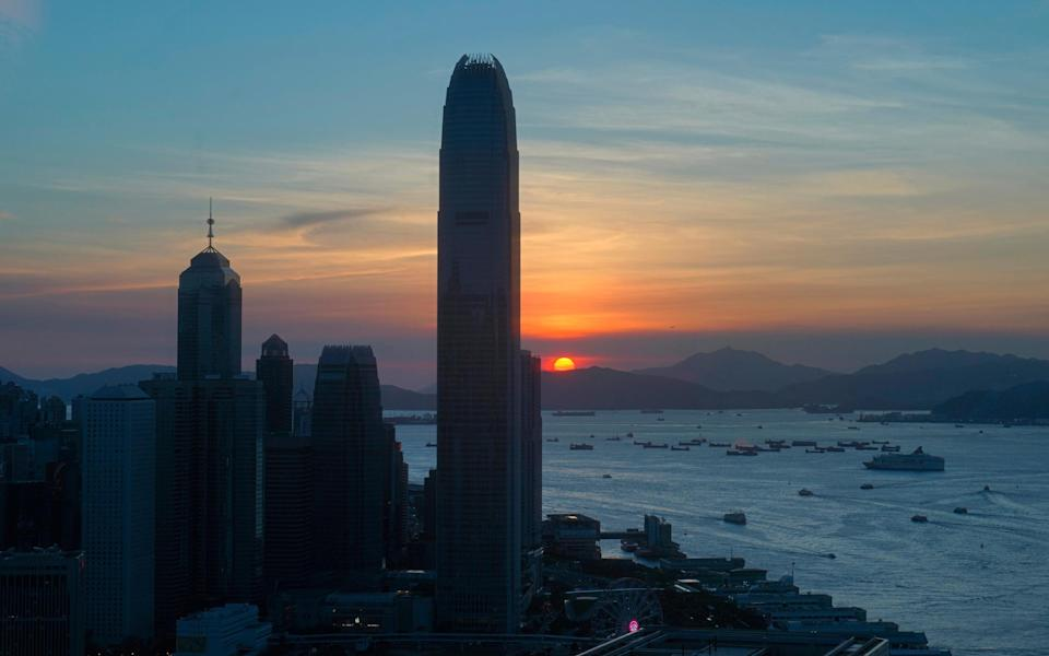 The sun sets in Hong Kong on Monday - AP