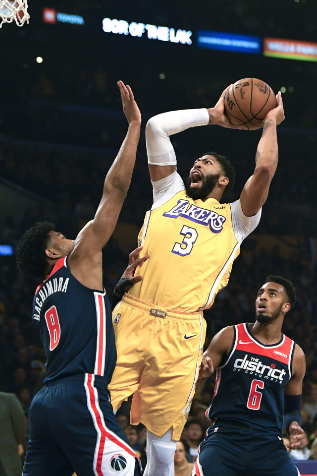 Los Angeles Lakers forward Anthony Davis, center, shoots as Washington Wizards forward Rui Hachimura, left, defends along with guard Troy Brown Jr. during the first half of an NBA basketball game Friday, Nov. 29, 2019, in Los Angeles. (AP Photo/Mark J. Terrill)