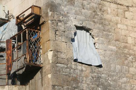 A curtain hangs out a hole in the wall in a damaged building in rebel-held besieged old Aleppo, Syria December 2, 2016. REUTERS/Abdalrhman Ismail