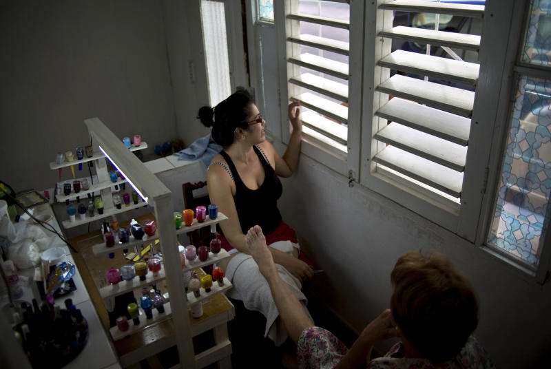 """In this Dec. 24, 2013 photo, Gisselle de la Noval speaks with a client through the window of her nail salon, which she runs out of her boyfriend's apartment where he previously ran a pizza joint in Havana, Cuba. Noval turned the space into a nail salon after her boyfriend's pizza joint failed. """"I donít miss the pizzeria, but I am sad it wasn't a success,"""" she says with a shrug. """"But I am young, so whatever. Now I'm dedicated to this."""" (AP Photo/Ramon Espinosa)"""