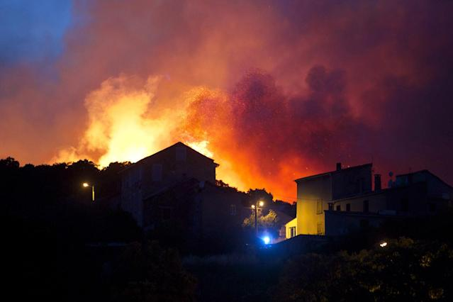 <p>A forest fire rages on a hillside above the village of Ortale in Corsica, France, July 24, 2017. Hundreds of firefighters are battling blazes fanned by high winds in more than a dozen zones in the Riviera region of southern France. (Raphael Poletti/AP) </p>