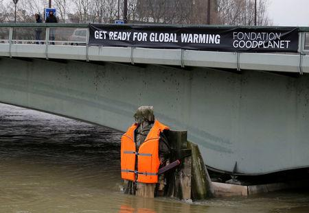 "A banner hangs from the Pont d'Alma bridge with the message, ""Get Ready for Global Warming"", above the Zouave soldier statue that wears a life vest as high waters from rain continue to cause the Seine River to overflow its banks, in Paris, France, February 4, 2018. REUTERS/Regis Duvignau"