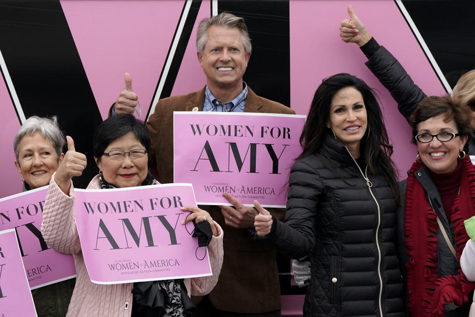 U.S. Rep. Roger Marshall, R-Kan., poses for a photo with a group of women attending a Concerned Women for America event outside a gun store in Kansas City, Kan. Wednesday, Oct. 21, 2020. Marshall is facing stiff competition from state Sen. Barbara Bollier in the race to fill an open Senate seat in Kansas. (AP Photo/Charlie Riedel)