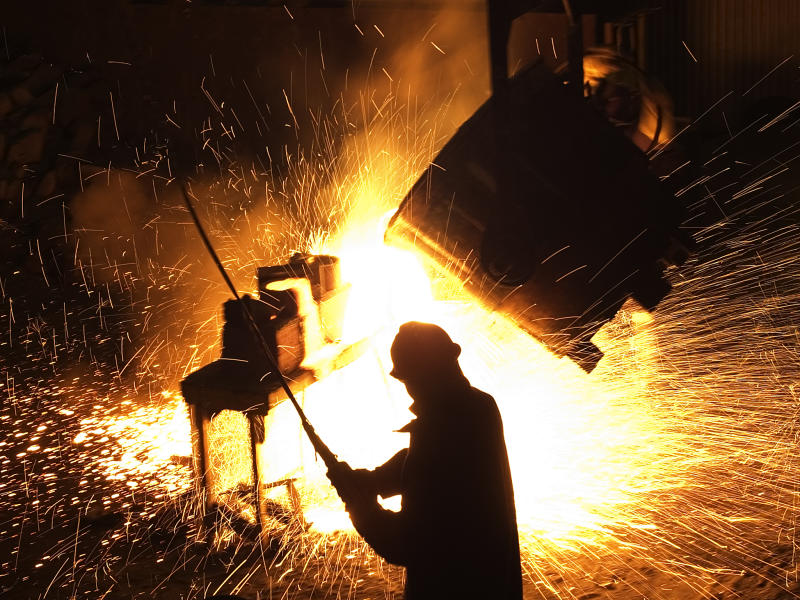 A man standing in front of a sparking steel