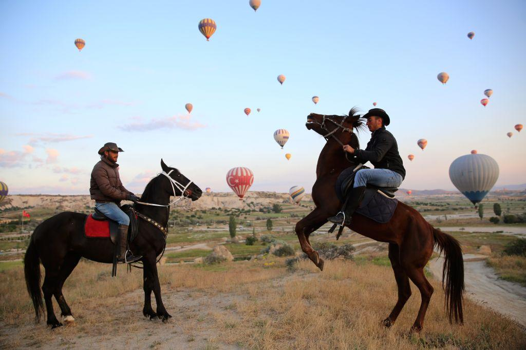 <p>Men ride horses among hot air balloons near fairy chimneys in Cappadocia in Turkey's Nevsehir Cappadocia known as 'The Land of Beautiful Horses', attract foreign and domestic tourists among the unique natural beauties. Cappadocia is preserved as a UNESCO World Heritage site and is famous for its chimney rocks, hot air balloon trips, underground cities and boutique hotels carved into rocks. (Behcet Alkan/Anadolu Agency/Getty Images) </p>