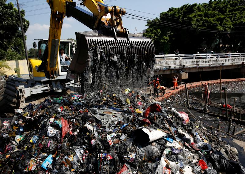 Government workers gather plastic and other debris for collection as an excavator removes the garbage from the Sekretaris River in Jakarta, Indonesia. (Photo: Darren Whiteside/Reuters)