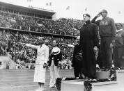 FILE - In this Aug. 3, 1936, file photo, gold medalist Jessie Owens, second right, salutes during the playing of the national anthem during the medal ceremony of the 100-meter final in Berlin. silver medalist Tinus Osendarp, third from right, of, Holland, and bronze medalist Ralph Metcalf, right, listen, along with a matron who holds a Nazi salute. The 1936 Games in Berlin, awarded about two years before Adolf Hitler became dictator, went ahead under Nazism. American track great Jesse Owens went on to win four gold medals, but he was only supposed to compete in three events, the 100 meters, 200 meters and long jump. (AP Photo/File)