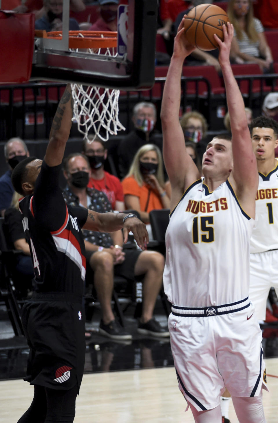 Denver Nuggets center Nikola Jokic, right, goes up for a dunk on Portland Trail Blazers forward Norman Powell, left during the first half of Game 4 of an NBA basketball first-round playoff series in Portland, Ore., Thursday, May 29, 2021. (AP Photo/Steve Dykes)