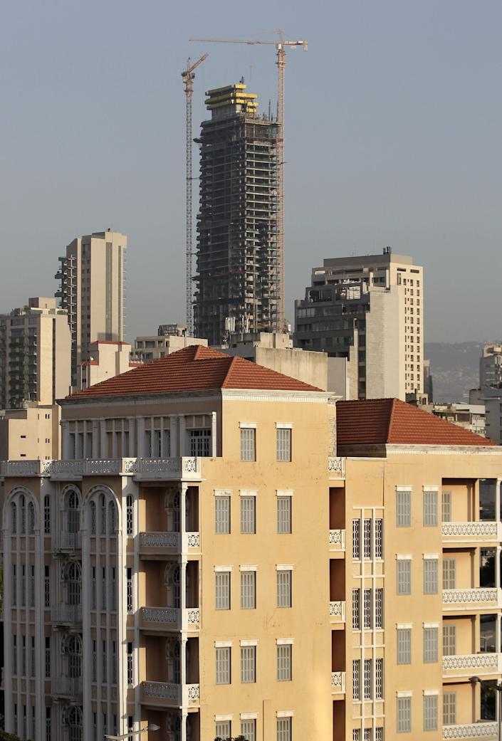In this April 8, 2014 photo, an old building with a traditional red brick roof, foreground, is overshadowed by the Beirut Sky tower under construction in Beirut, Lebanon. One by one, the old traditional houses of Beirut are vanishing as luxury towers sprout up on every corner, altering the city's skyline almost beyond recognition. While Lebanon's real estate sector has developed to become one of the country's success stories, many say it is coming at the expense of Lebanon's identity and heritage. (AP Photo/Hussein Malla)