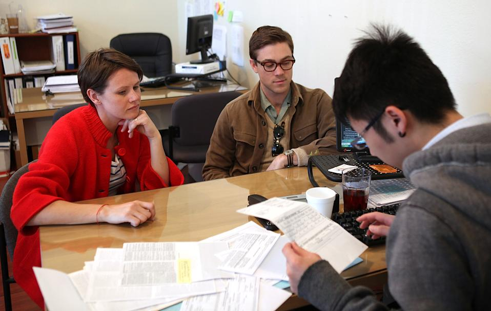 Drew Darmon (R) and his wife Erika Darmon (L) look on as they receive tax preparation assistance from a tax preparer. (Photo: Justin Sullivan/Getty Images)