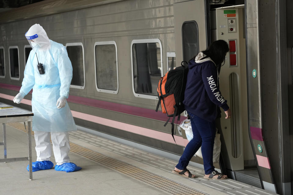 A COVID-19 patient gets into a train at Rangsit train station in Pathum Thani Province, Thailand to head to her hometown Tuesday, July 27, 2021. Thai authorities began transporting some people who have tested positive with the coronavirus from Bangkok to their hometowns on Tuesday for isolation and treatment, to alleviate the burden on the capital's overwhelmed medical system. (AP Photo/Sakchai Lalit)
