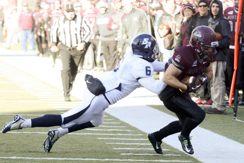 San Diego safety Matt Miller (6) pushes Montana wide receiver Kevin Berland (84) out of bounds near the end zone during the first half of an NCAA college football playoff game, Saturday, Nov. 29, 2014, in Missoula, Mont. (AP Photo/Lido Vizzutti)