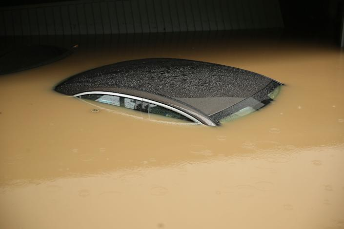 A car, submerged up to the roof in water, is parked in front of a flooded garage in Duesseldorf, Germany, Wednesday morning, July 14, 2021. Storms caused widespread flooding across central Germany overnight, with authorities warning that more rain is on the way.