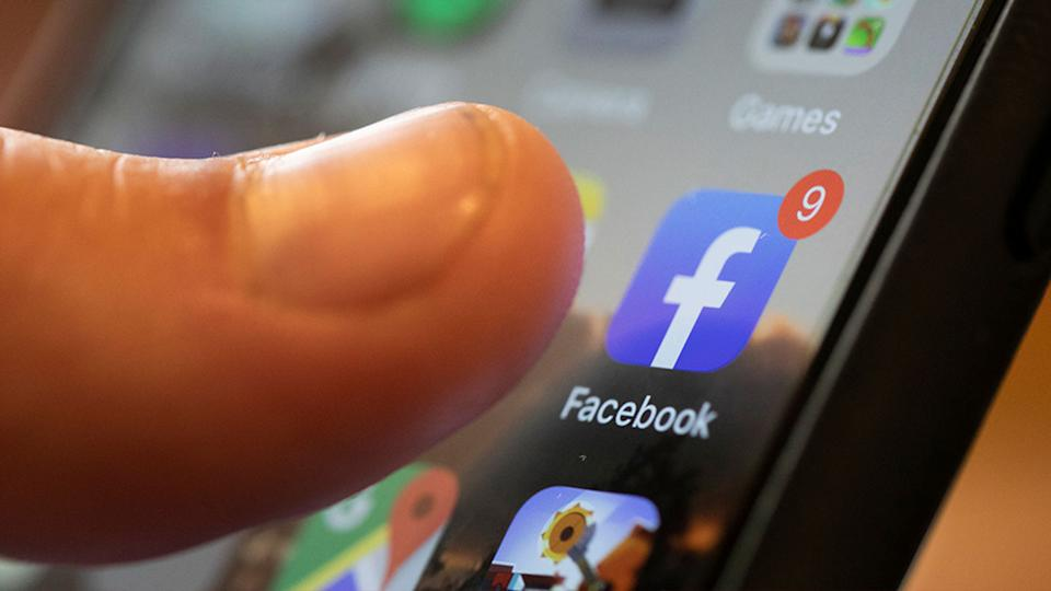 A Facebook icon appears on a smartphone screen with a thumb hovering over it.