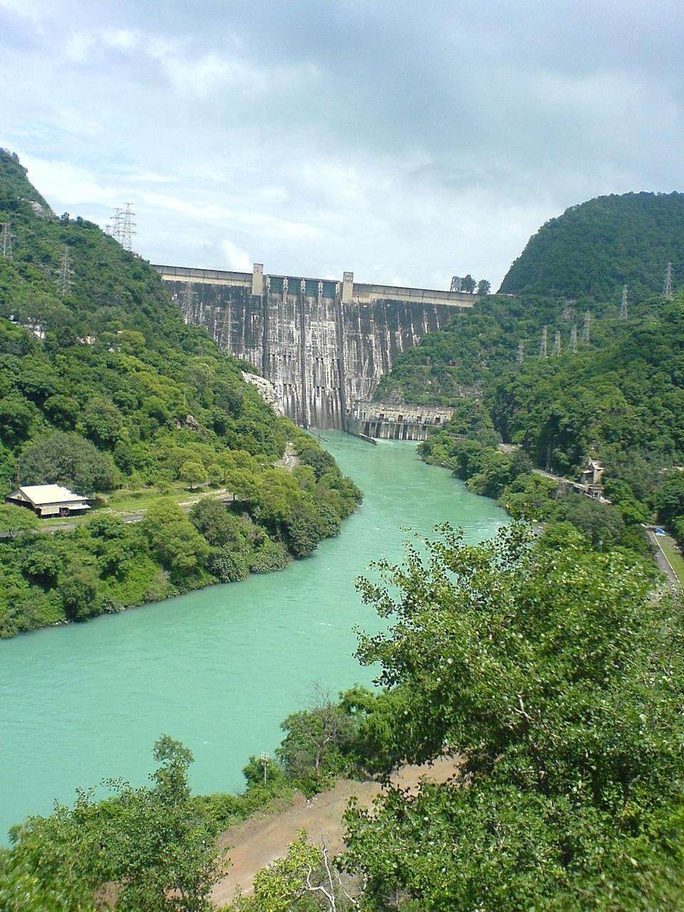 """Bhakra Dam is a concrete gravity dam across the Sutlej River, and is near the border between Punjab and Himachal Pradesh in northern India. The dam, located at a gorge near the (now submerged) upstream Bhakra village in Bilaspur district of Himachal Pradesh, is Asia's second highest at 225.55 m (740 ft) high next to the 261m Tehri Dam. The length of the dam (measured from the road above it) is 518.25 m; it is 9.1 m broad. Its reservoir, known as the """"Gobind Sagar"""", stores up to 9.34 billion cubic meters of water, enough to drain the whole of Chandigarh, parts of Haryana, Punjab and Delhi.The 90 km long reservoir created by the Bhakra Dam is spread over an area of 168.35 km2. In terms of storage of water, it withholds the second largest reservoir in India, the first being Indira Sagar dam in Madhya Pradesh with capacity of 12.22 billion cu m.Nangal dam is another dam downstream of Bhakra dam. [Photo by KawalSingh at en.wikipedia (Transferred from en.wikipedia - Public domain from Wikimedia Commons]"""