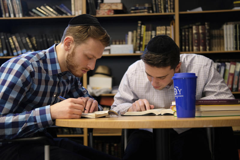 Yeshiva University students Aaron Heideman, left, and Marc Shapiro study in the university's library in New York, Thursday, Dec. 12, 2019. They praised President Donald Trump's executive order to expand the scope of potential anti-Semitism complaints on U.S. college campuses. They said they worry that friends attending other universities might be targeted by anti-Semitic attacks and that this could help protect them. (AP Photo/Luis Andres Henao)