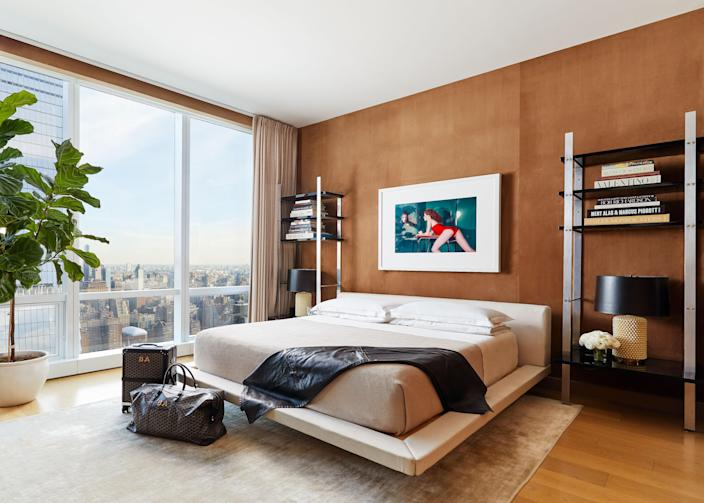 """Says Atwood, """"We wanted our bedroom to feel like a jewel box, and we decided to use a custom velvet wallpaper not only on the walls but on the ceiling too."""" An All Modern bed with <a href=""""https://kassatex.com/"""" rel=""""nofollow noopener"""" target=""""_blank"""" data-ylk=""""slk:Kassatex"""" class=""""link rapid-noclick-resp"""">Kassatex</a> linens is framed by vintage Milo Baughman shelving units. Of the countless photographs the two have collected, this Guy Bordain image of an alluring woman gets a prime spot. Says Deutsch, """"Most everybody has something that's serene above their bed—a big horse head or a landscape. We went for this bold image of this chick leaning over and sexy. And by the way, we're not even straight, but it's just exciting!"""" A leather <a href=""""https://www.hermes.com/us/en/"""" rel=""""nofollow noopener"""" target=""""_blank"""" data-ylk=""""slk:Hermès"""" class=""""link rapid-noclick-resp"""">Hermès</a> stable blanket and monogrammed <a href=""""https://catalogue.goyard.com/en/"""" rel=""""nofollow noopener"""" target=""""_blank"""" data-ylk=""""slk:Goyard"""" class=""""link rapid-noclick-resp"""">Goyard</a> luggage add to the urban sophistication of the room."""