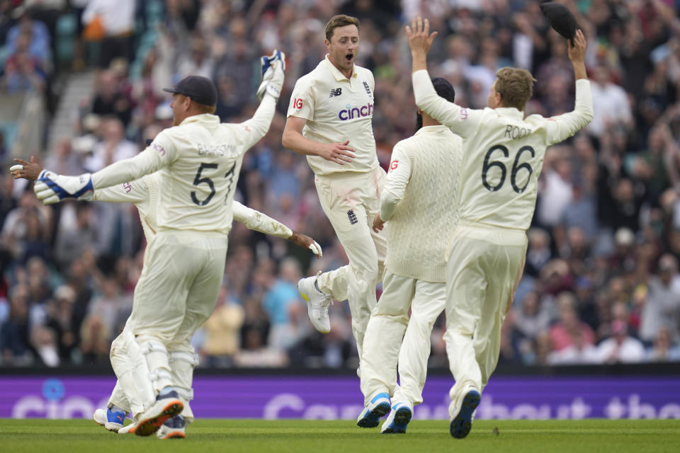 England's Ollie Robinson, centre, jumps as he celebrates taking the wicket of India's Cheteshwar Pujara on day three of the fourth Test match at The Oval cricket ground in London, Saturday, Sept. 4, 2021. (AP Photo/Kirsty Wigglesworth)
