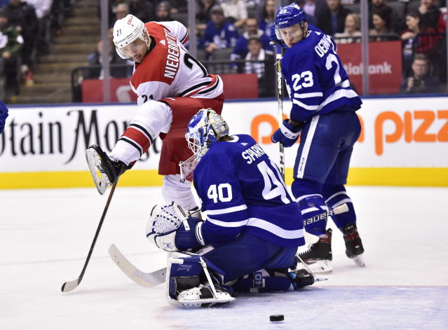 Carolina Hurricanes right wing Nino Niederreiter (21) looks to tip the puck past Toronto Maple Leafs goaltender Garret Sparks (40) as Toronto Maple Leafs' Travis Dermott (23) defends during the third period of an NHL hockey game, Tuesday, April 2, 2019, in Toronto. There was no goal on the play. (Frank Gunn/The Canadian Press via AP)