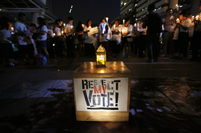 "Members of Thailand's ""White Shirt"" movement attend a candlelight vigil to demand democratic elections and political reforms in Bangkok, Thailand, Friday, Jan. 31, 2014. Thailand's general election is scheduled for Sunday, Feb. 2, 2014, but the main opposition Democrat Party is boycotting it, and its supporters seeking to scuttle it by blocking access to polling stations throughout Bangkok. The ""White Shirt"" movement is intended to give voice to Thais who are neither anti-government protesters nor pro-government ""Red Shirt"" activists. (AP Photo/Wally Santana)"