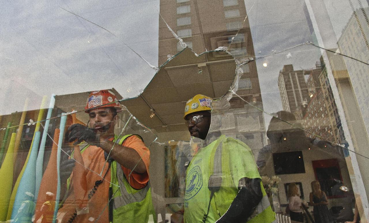 Construction workers remove window display items near the shattered window of Kolb Art Gallery following damage from an intentional underground explosion on the Second Avenue subway project on East 72nd on Tuesday, Aug. 21, 2012. (AP Photo/Bebeto Matthews)