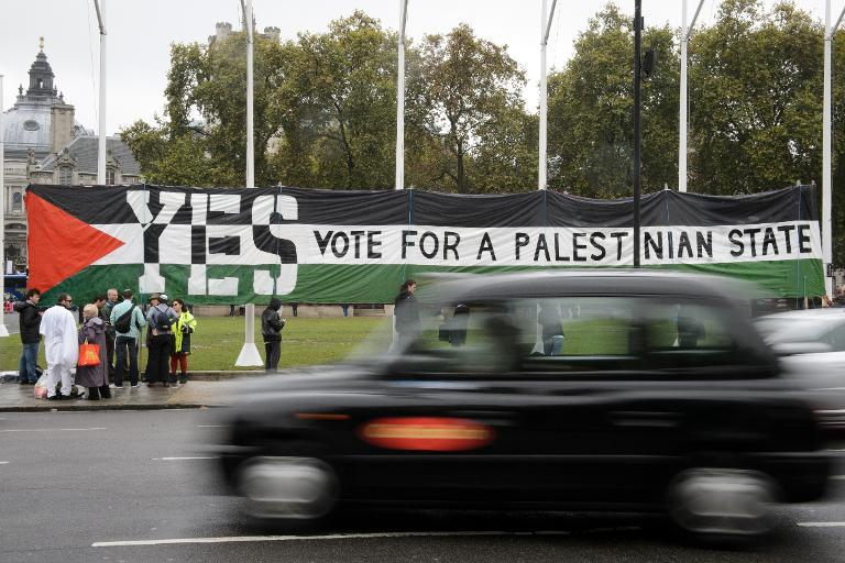 Pro-Palestinian supporters position a giant banner calling for a recognised Palestinian State, in Parliament Square, central London on October 13, 2014