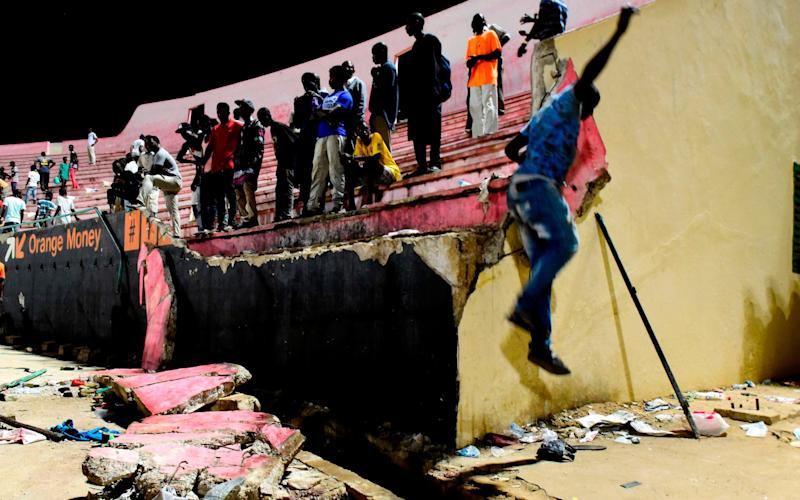 People look at the scene after a wall collapsed at Demba Diop  - AFP