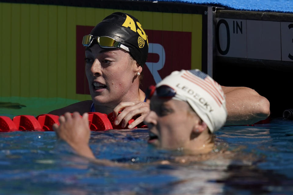 Allison Schmitt, left, and Katie Ledecky look at the results after competing in the women's 200-meter final at the TYR Pro Swim Series swim meet Friday, April 9, 2021, in Mission Viejo, Calif. Ledecky won the final and Schmitt came in second. (AP Photo/Ashley Landis)