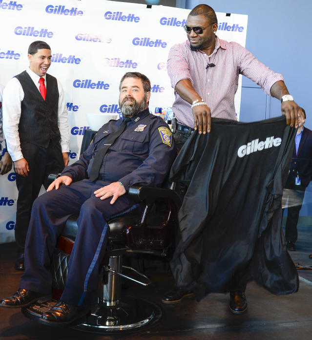 IMAGE DISTRIBUTED FOR GILLETTE - Red Sox designated hitter David Ortiz helps local legend Officer Steve Horgan celebrate his team's World Series win at Gillette World Shaving Headquarters, on Monday, Nov. 4, 2013 in Boston. (Photo by John Cetrino/Invision for Gillette/AP Images)