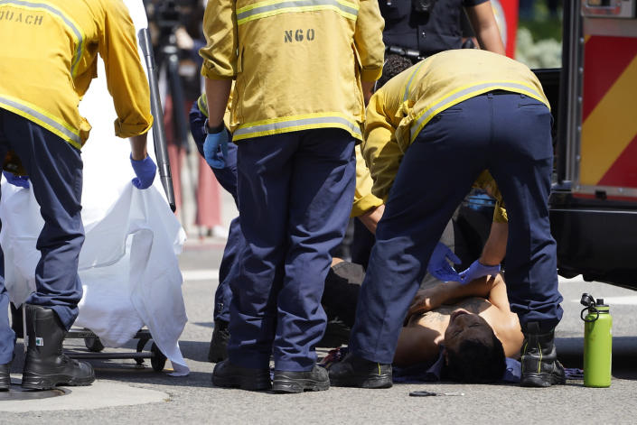 Los Angeles Fire department paramedics care for an injured demonstrator, who was stabbed in the chest during clashes between anti-vaccination demonstrators and counter-protesters during an anti-vaccination protest in front of the City Hall in Los Angeles on Saturday, Aug. 14, 2021. A man was stabbed and a reporter was attacked Saturday at a protest against vaccine mandates on the south lawn of Los Angeles' City Hall after a fight broke out between the protesters and counter-protesters, the Los Angeles Police Department and local media said. ( AP Photo/Damian Dovarganes)