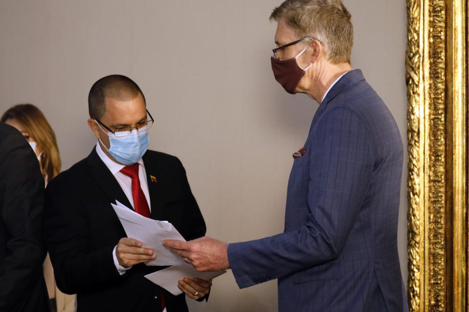 """Robert Schuddeboom, Charge d'Affaires for the Netherlands, right, receives a protest letter from Venezuelan Foreign Minister Jorge Arreaza at the Foreign Ministry headquarters in Caracas, Venezuela, Wednesday, Feb. 24, 2021, amid the COVID-19 pandemic. The meeting was called after the EU sanctioned an additional 19 Venezuelans for """"undermining democracy and the rule of law"""" in Venezuela and the National Assembly declared the EU ambassador """"persona non grata."""" (AP Photo/Ariana Cubillos)"""