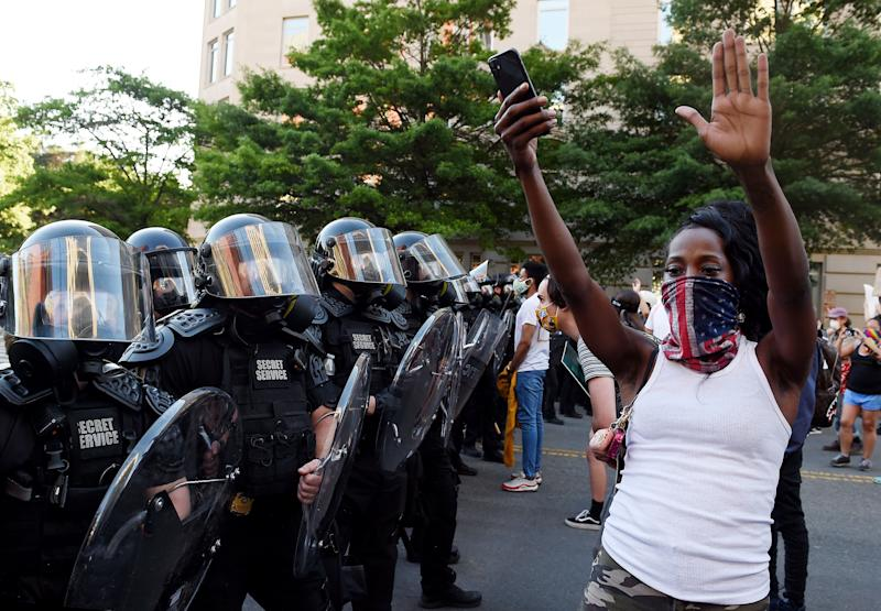 A protester stands, arms in the air, in front of a row of officers during a demonstration near the White House on June 1. (Photo: OLIVIER DOULIERY/AFP via Getty Images)