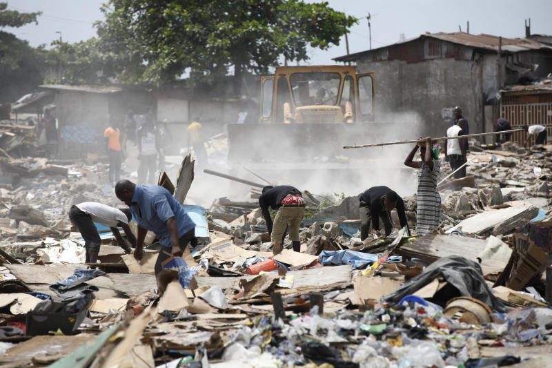 In this image taken Thursday Feb. 28, 2013 people search through the rubble of demolished houses at Ijora Badia slum in Lagos, Nigeria, Thursday, Feb. 28, 2013. The bulldozers arrived at dawn to this neighborhood of shanty homes and concrete buildings in Nigeria's largest city, followed by police officers in riot gear carrying Kalashnikov assault rifles. The police banged on doors, corralling the thousands who live in Ijora-Badia off to the side as the bulldozers' blades tore through scrap-lumber walls, its track grinding the possessions inside into the black murk of swamp beneath it. It left behind only a field of debris that children days later picked through, their small hands dodging exposed rusty nails to pull away anything of value left behind. (AP Photo/Sunday Alamba)