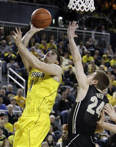Michigan guard Stu Douglass (1) shoots over Purdue guard Ryne Smith (24) during the first half of an NCAA college basketball game at Crisler Center in Ann Arbor, Mich., Saturday, Feb. 25, 2012. (AP Photo/Carlos Osorio)