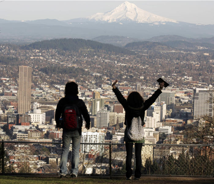 "FILE - In this file photo from Feb. 26, 2008, a young couple enjoys the view of Mount Hood looming over downtown on a spring-like day in Portland, Ore. A famous quip by Fred Armisen on the television show ""Portlandia"" led Portland State University researchers to investigate the reality behind the comment. The quirky IFC network series pokes fun at the Oregon city's many eccentricities. (AP Photo/Don Ryan, File)"