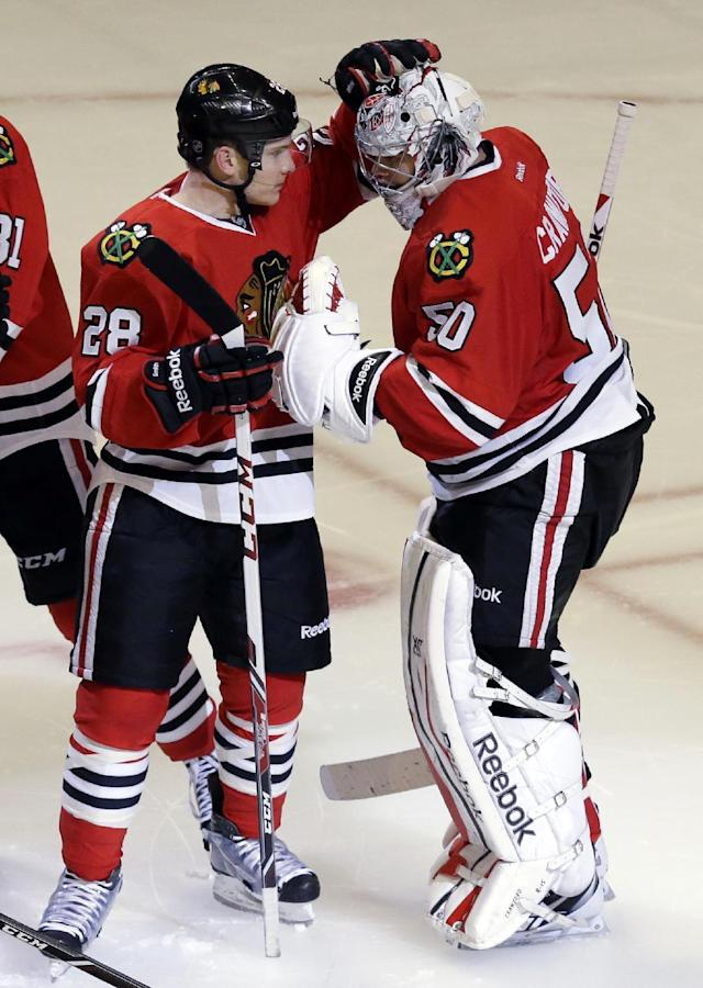 Chicago Blackhawks goalie Corey Crawford, right, celebrates with Ben Smith after the Blackhawks defeated the Phoenix Coyotes 5-4 in a shootout during an NHL hockey game in Chicago, Thursday, Nov. 14, 2013. (AP Photo/Nam Y. Huh)