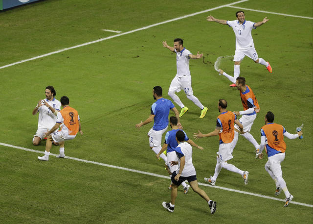 Greece's Giorgos Samaras, far left, celebrates with his team after he scored on a penalty kick in the final minutes during the group C World Cup soccer match between Greece and Ivory Coast at the Arena Castelao in Fortaleza, Brazil, Tuesday, June 24, 2014. Greece beat Ivory Coast 2-1. (AP Photo/Sergei Grits)