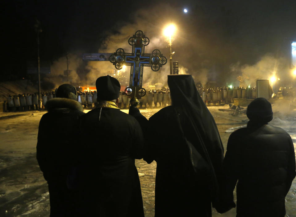 """Orthodox priests pray as they stand between pro-European Union activists and police lines in central Kiev, Ukraine, early Friday, Jan. 24, 2014. A top Ukrainian opposition leader on Thursday urged protesters to maintain a shaky cease-fire with police after at least two demonstrators were killed in clashes this week, but some in the crowd appeared defiant, jeering and chanting """"revolution"""" and """"shame."""" (AP Photo/Sergei Grits)"""