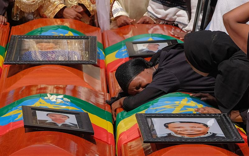 A woman lays on the coffin of her loved one during